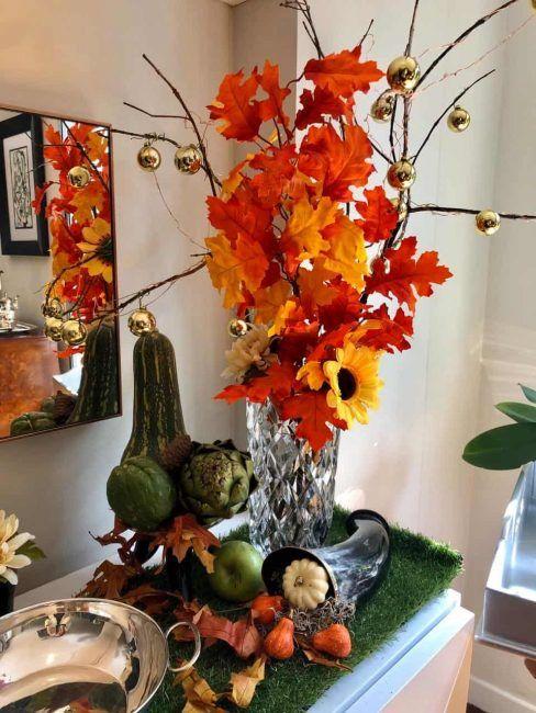 Hojas secas en un florero con algunas bolitas doradas acompañadas de pequeñas calabazas, velas y frutas en un sideboard, decoran una esquina para celebrar Halloween.