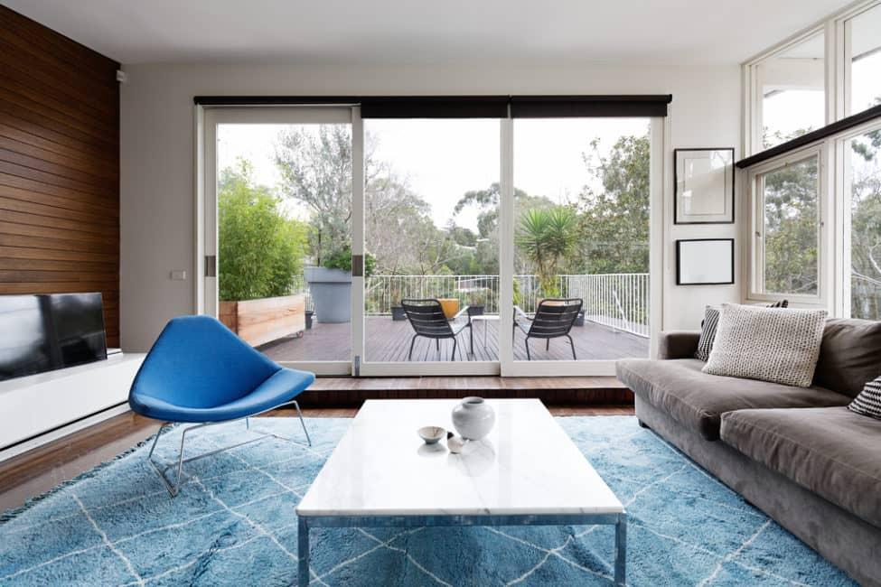Combina un sofá neutro con un toque de azul para darle vistosidad al espacio